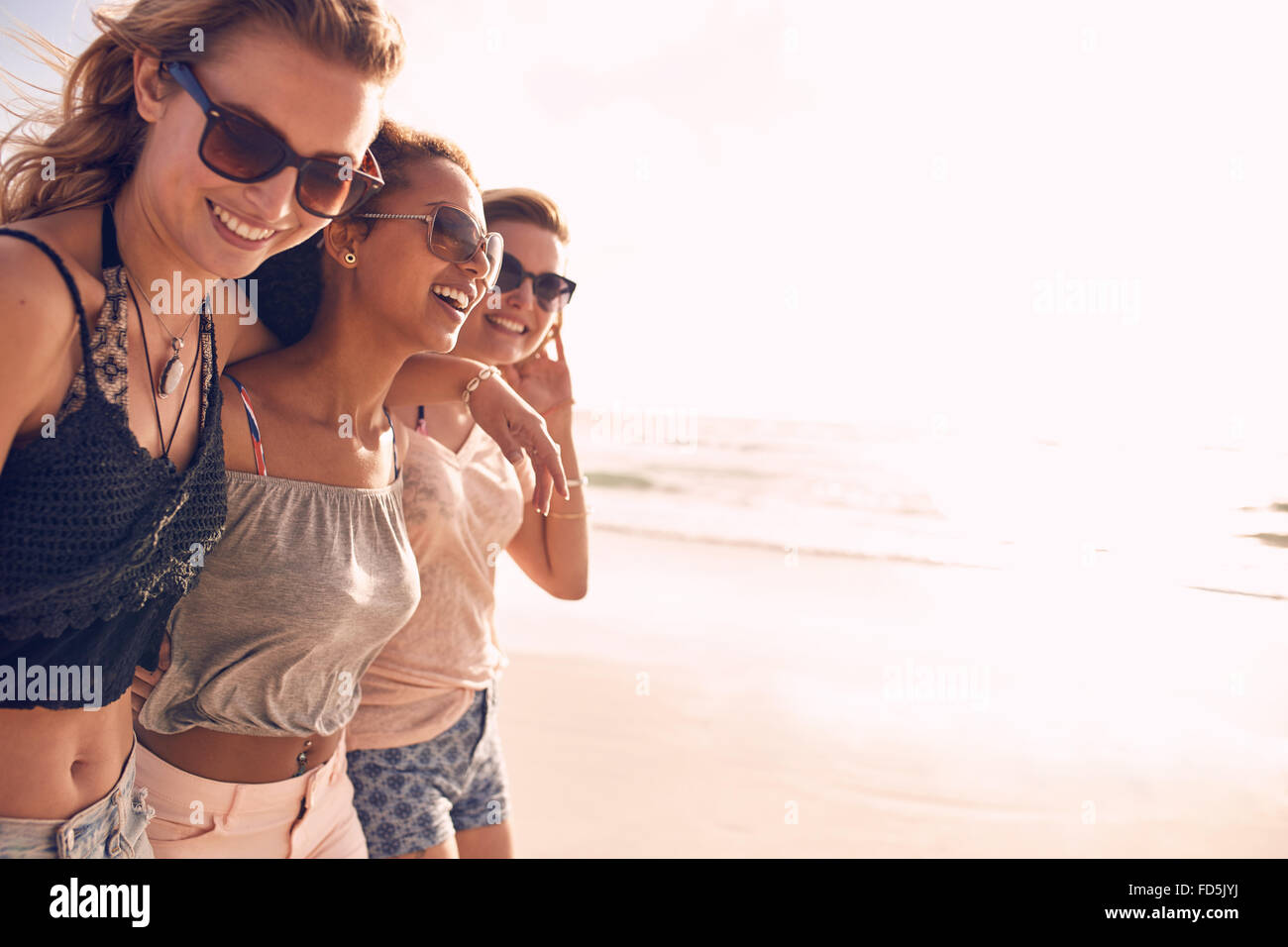 Group of beautiful young women strolling on a beach. Three friends walking on the beach and laughing on a summer - Stock Image