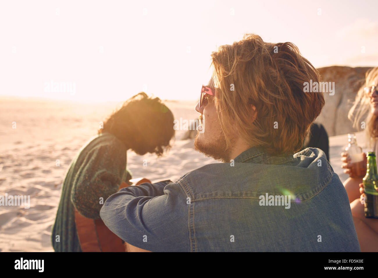 Young man enjoying a summer day at the beach with group of friends in background. Young people enjoying a day on - Stock Image