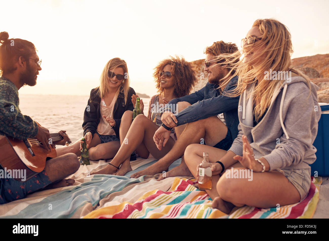 Young friends enjoying a beach party with music and drinks. Young man playing guitar with his friends drinking beer - Stock Image