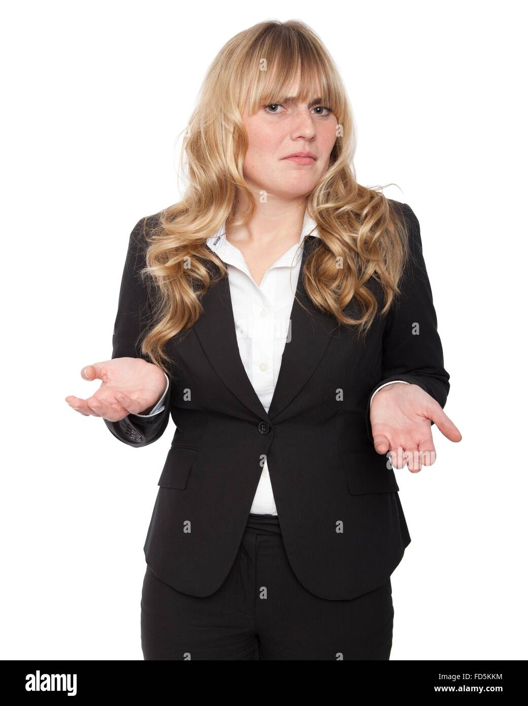 Young businesswoman shrugging her shoulders in ignorance, to show she does not know the answer and could not care. - Stock Image