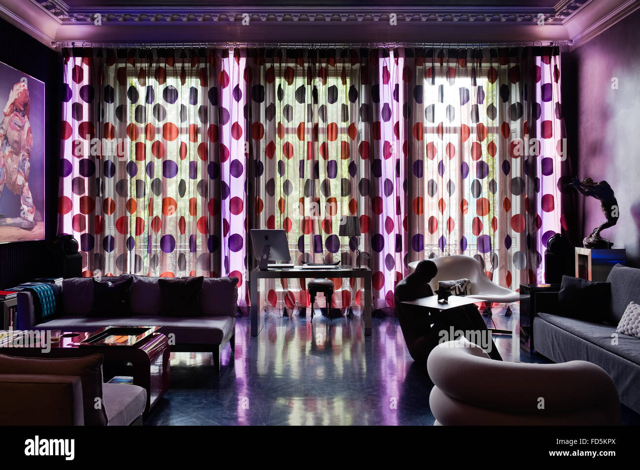 Desk in window backlit with red and purple spotted curtains and blue neon light, London apartment - Stock Image