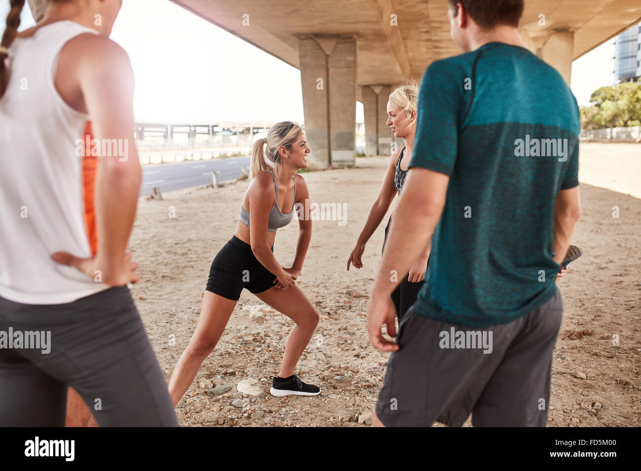 Fit young woman with running club group stretching after a run. Young people going stretching workout after a morning - Stock Image
