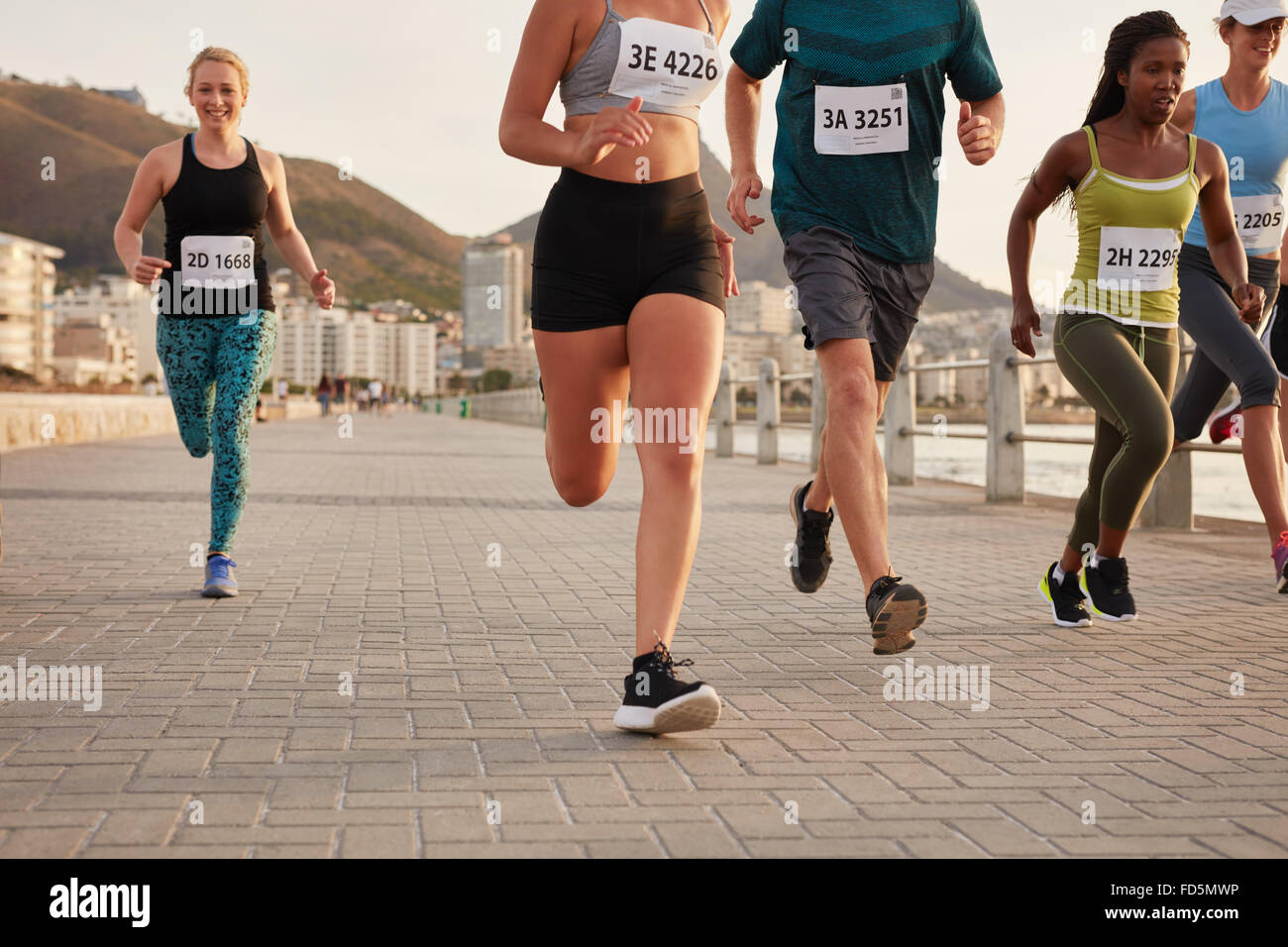 Diverse group of runners competing in a race. Athletes sprinting on a street along the sea. - Stock Image