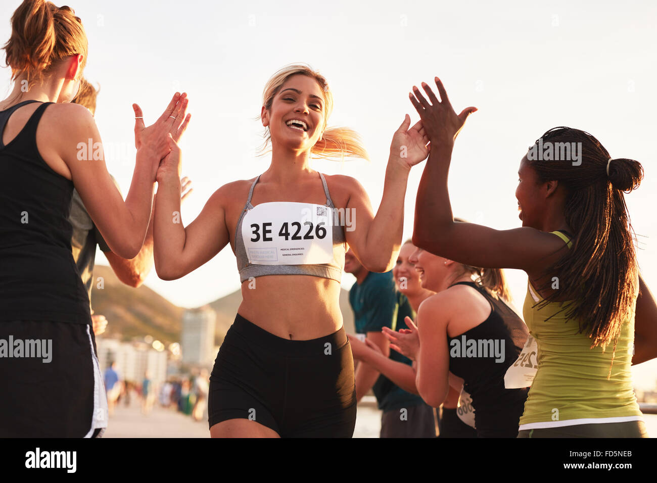 Multi ethnic group of young adults cheering and high fiving a female athlete crossing finish line. Sportswoman giving - Stock Image