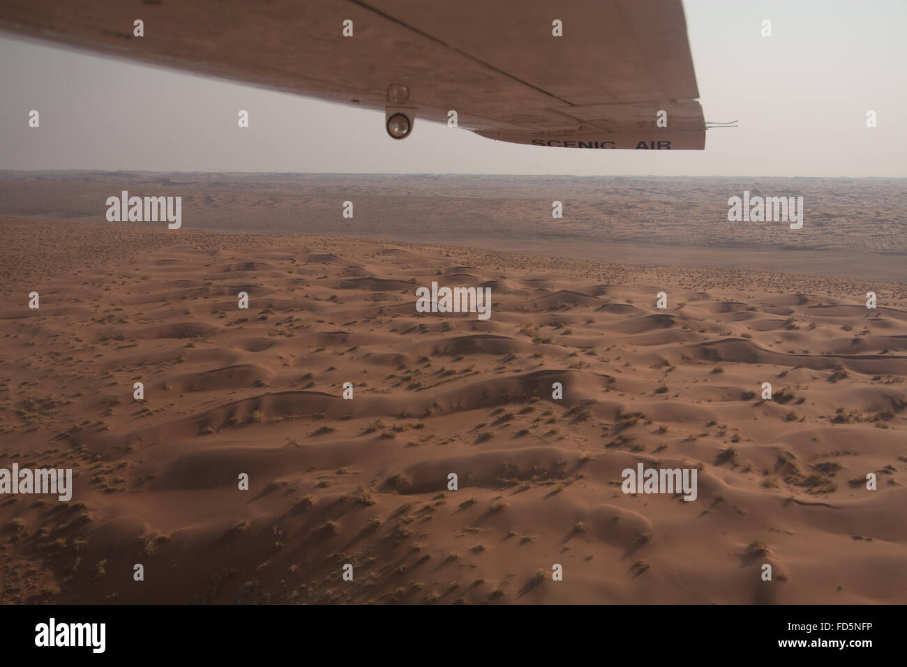 Cropped Image Of Airplane Flying Over Desert - Stock Image