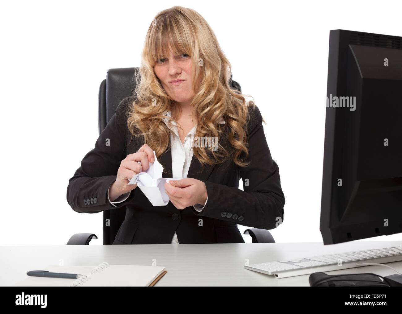 Disgusted businesswoman sitting at her desk ripping up a paper document with a grimace showing her dissatisfaction - Stock Image