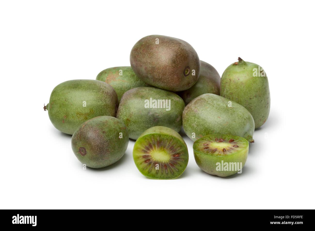 Whole and half kiwi berries on white background - Stock Image
