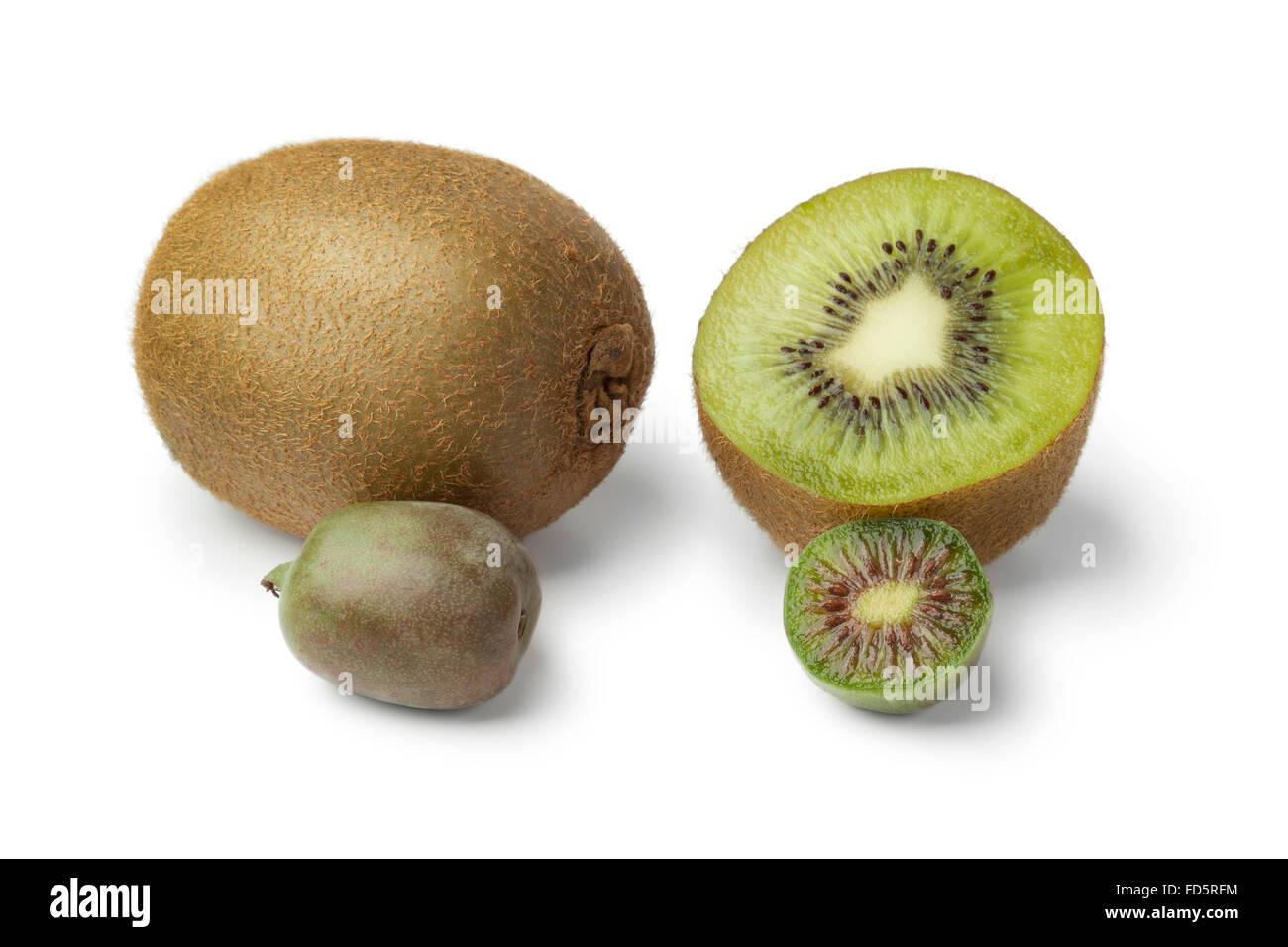 Whole and half kiwi fruit and kiwi berry on white background - Stock Image