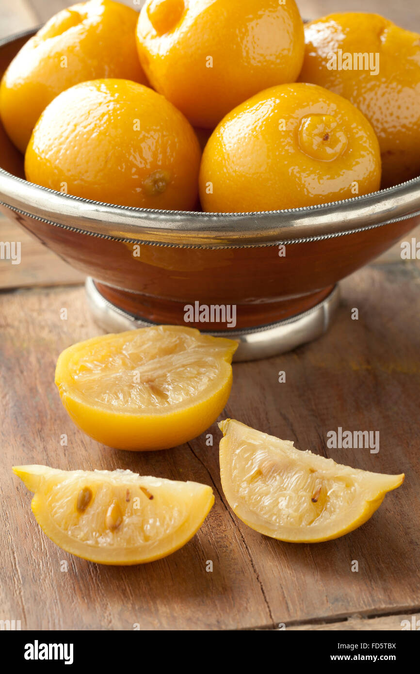 Whole and half preserved Moroccan pickled lemons in a bowl - Stock Image