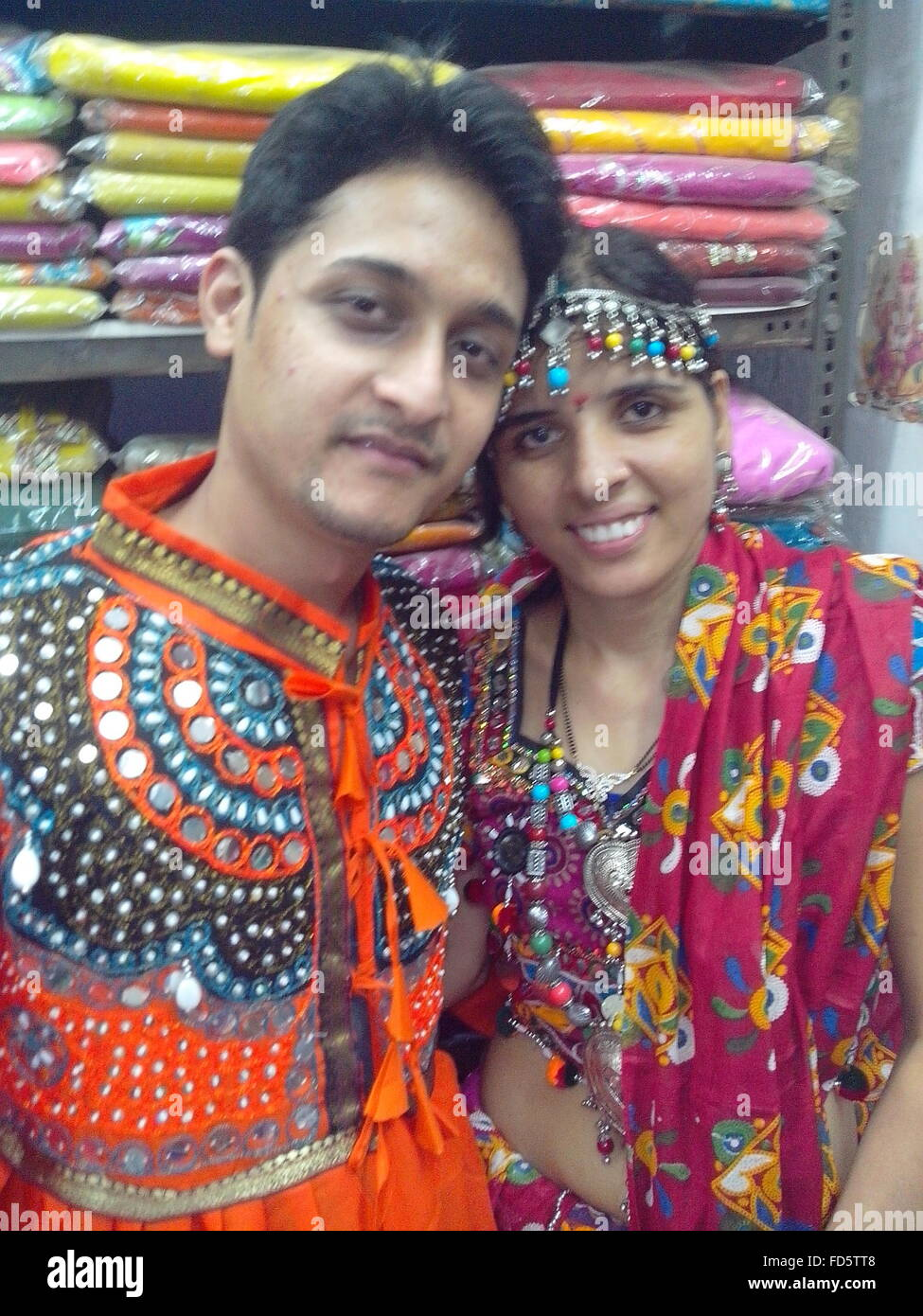 Portrait Of Smiling Young Couple Wearing Traditional Clothe While Standing In Shop - Stock Image