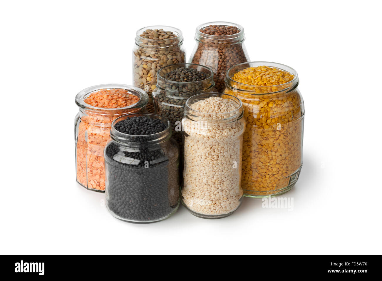 Variety of dried lentils in glass pots on white background - Stock Image