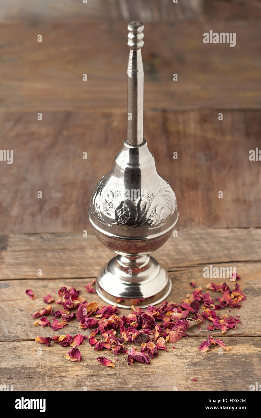 Moroccan rose water sprinkler and petals on wooden table - Stock Image