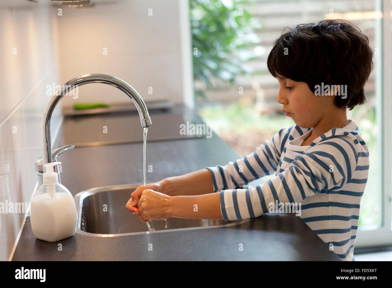 Eight year old boy washing hands in the kitchen - Stock Image