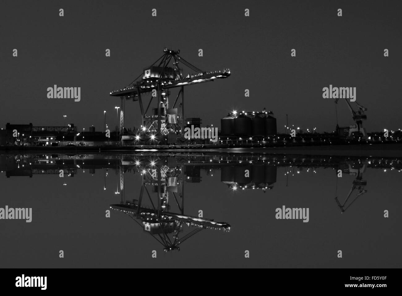 Harbor Cranes Reflecting In Water - Stock Image