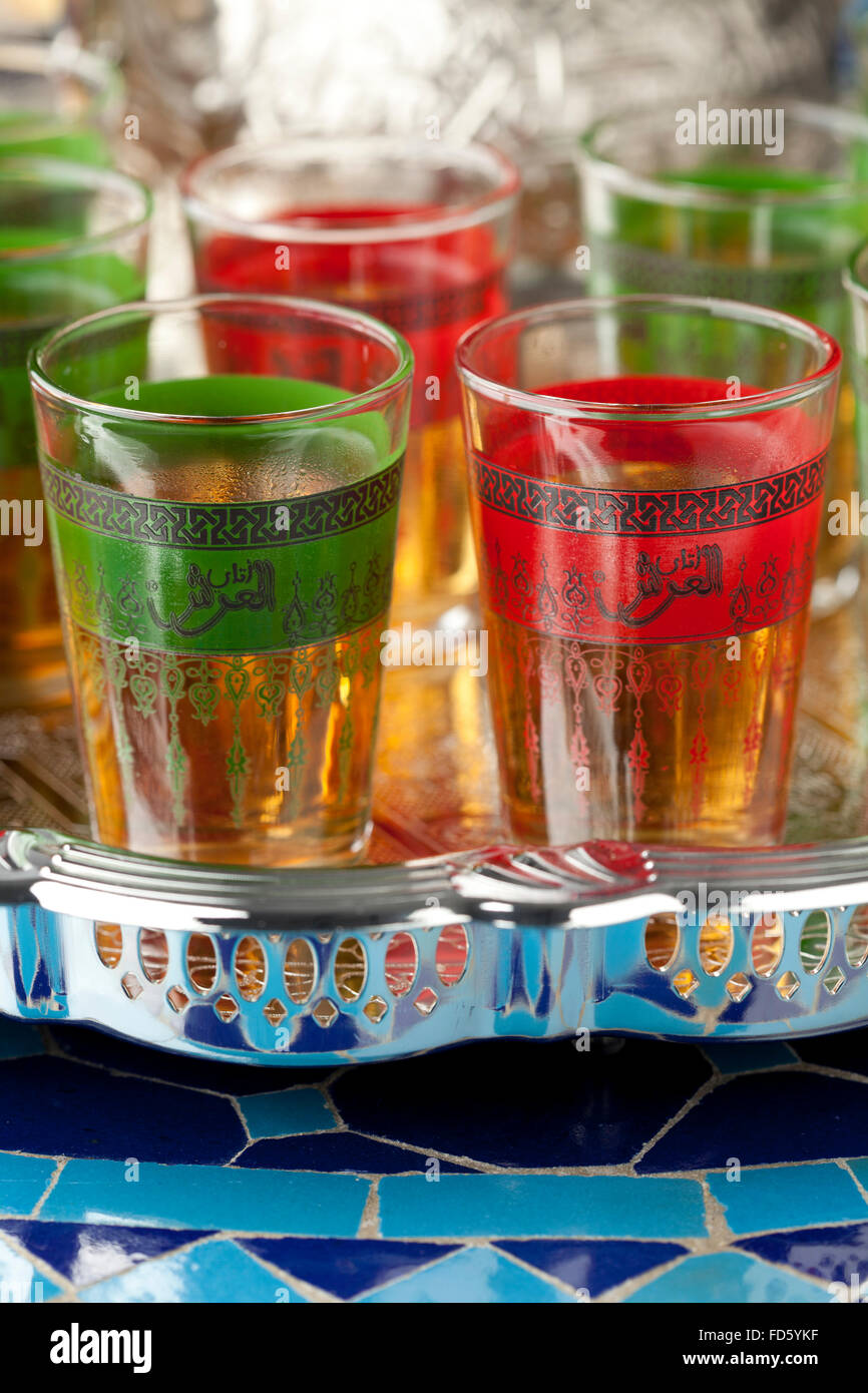Moroccan tea glasses  in the colors of the Moroccan flag with in Arabic letters written tea - Stock Image