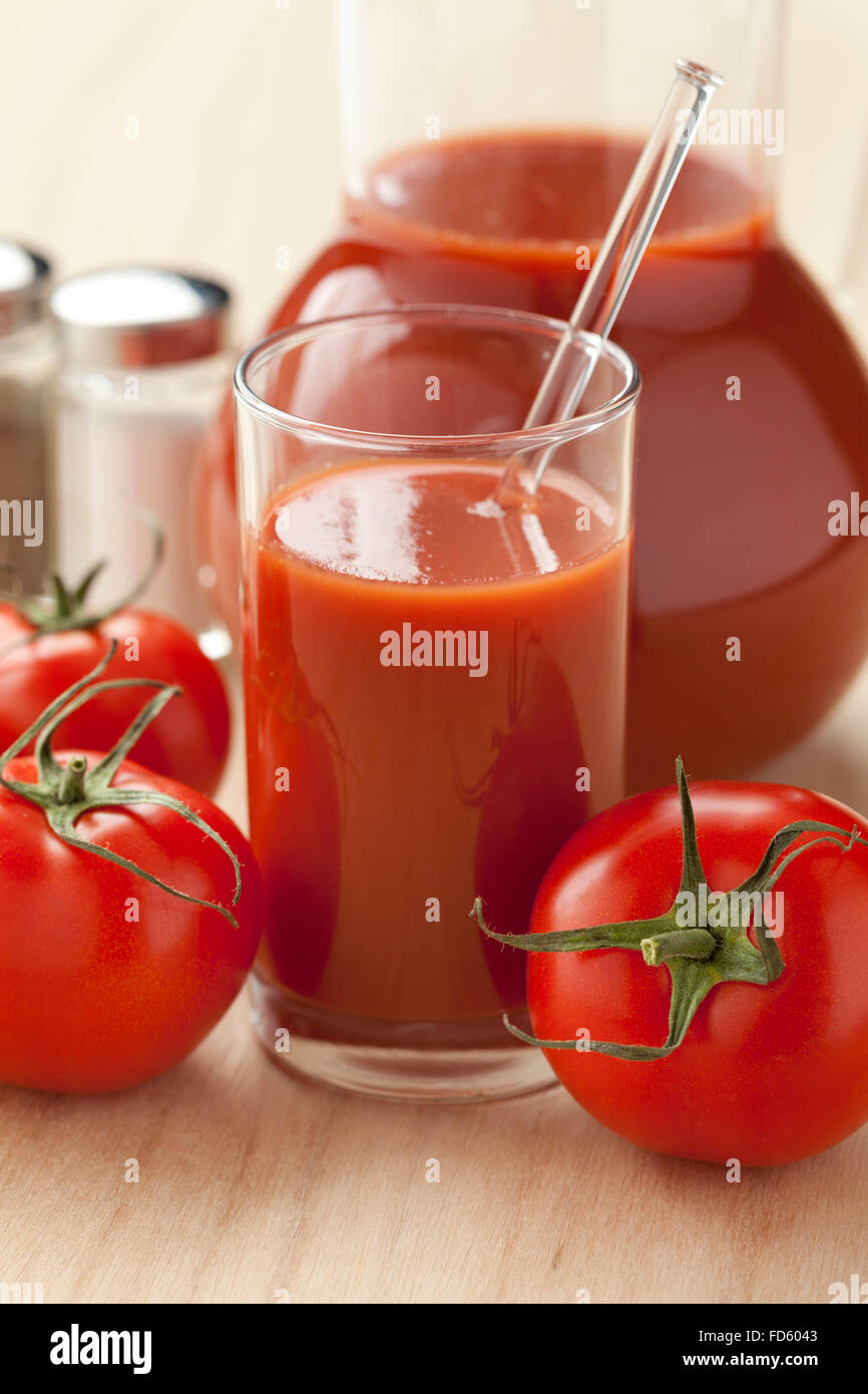 Fresh tomato juice in a jar and glass - Stock Image