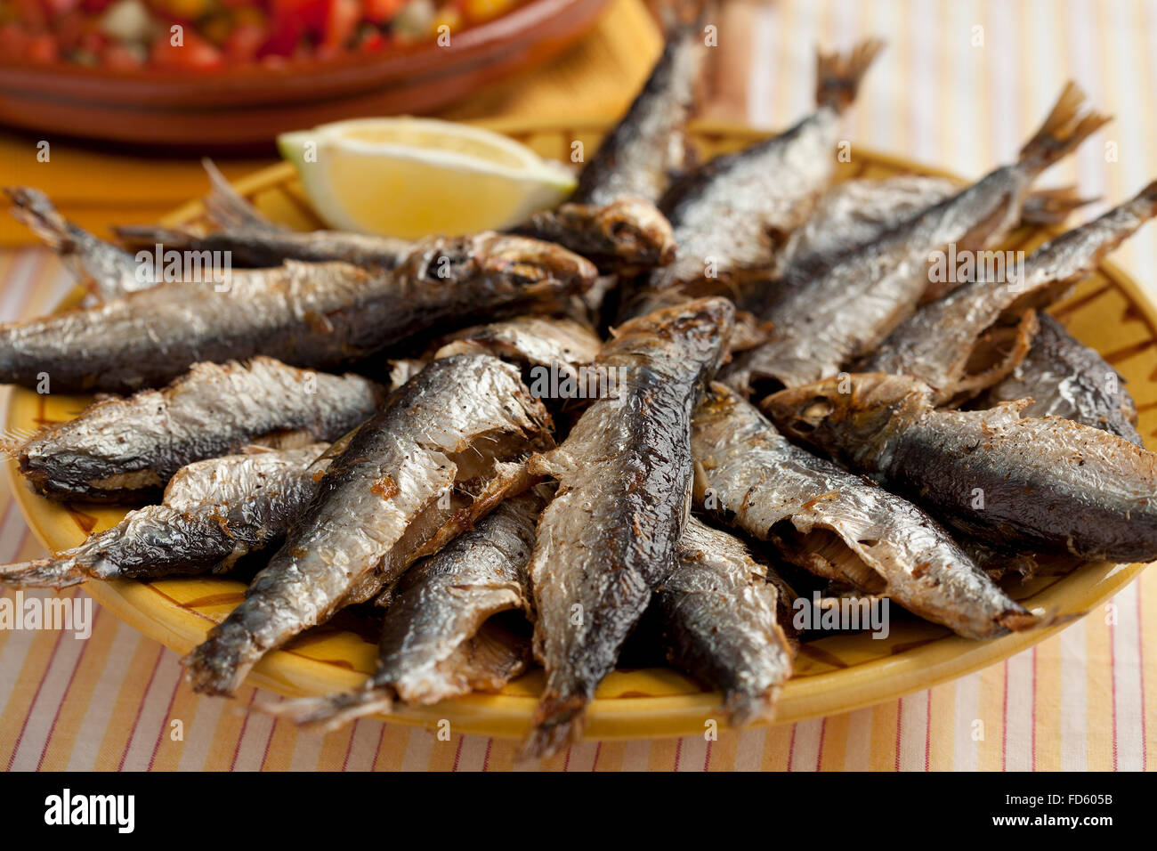 Fresh barbecued sardines on a dish - Stock Image