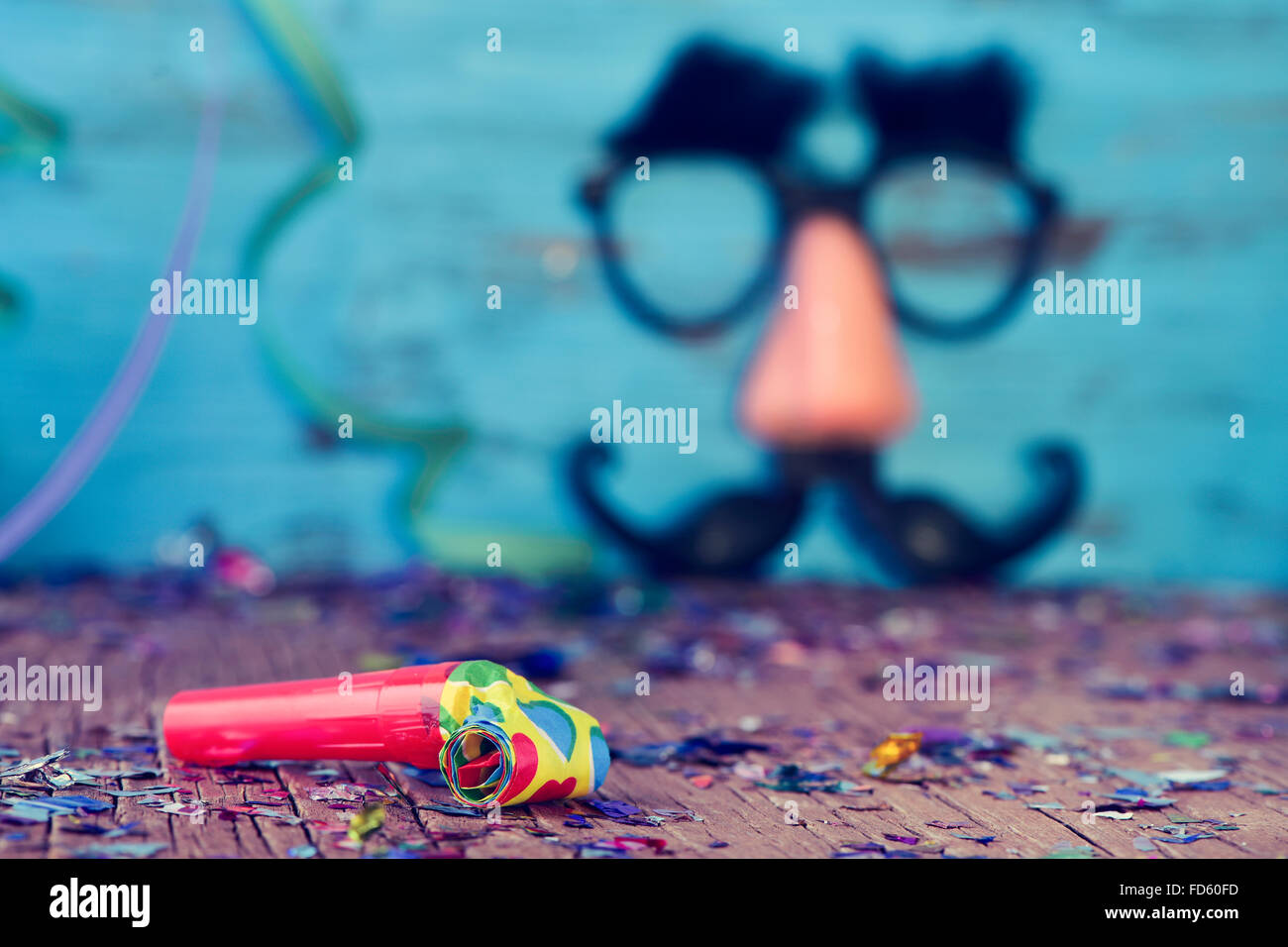 closeup of a party horns on a wooden surface full of confetti and streamers, and a pair of fake black glasses with - Stock Image