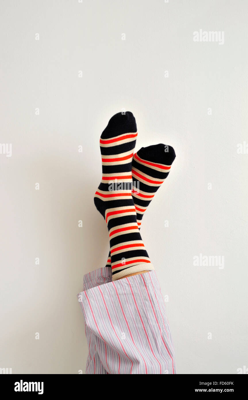 closeup of a young man in pajamas wearing colorful striped socks with his feet against the wall - Stock Image