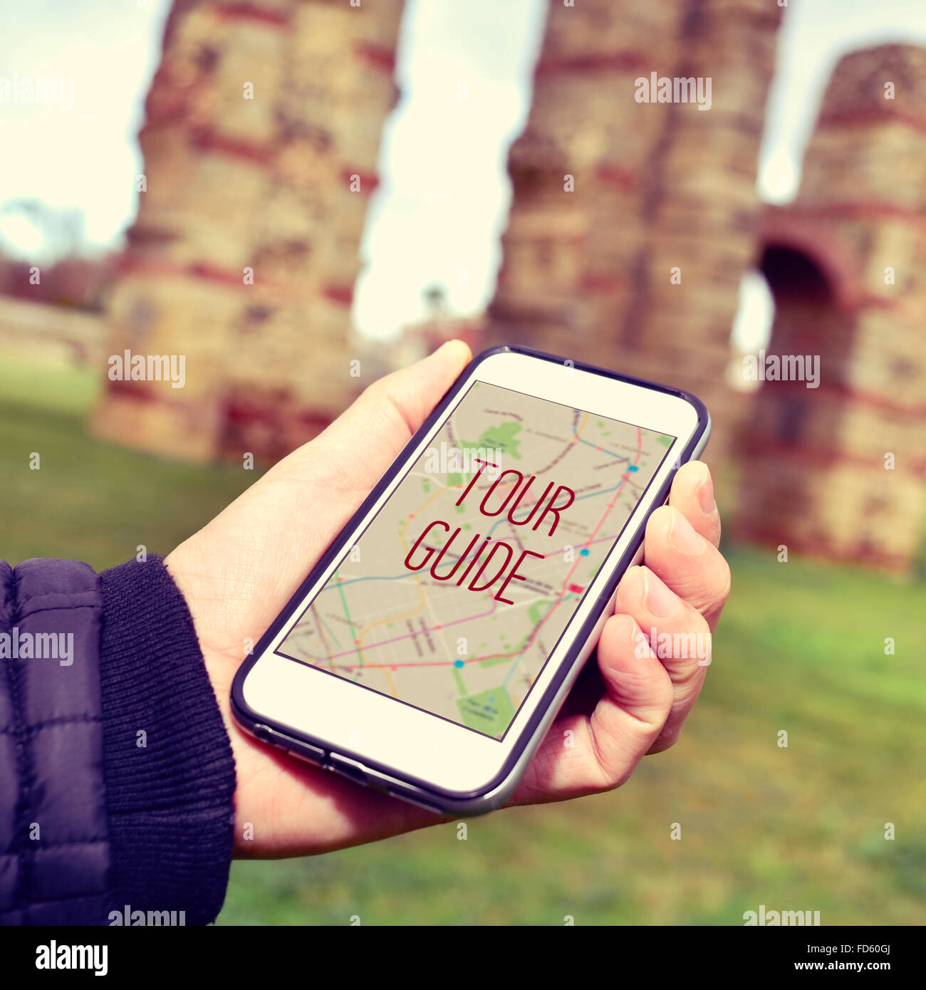 closeup of a young caucasian man with a smartphone with the text tour guide in its screen, in front of some ancient - Stock Image