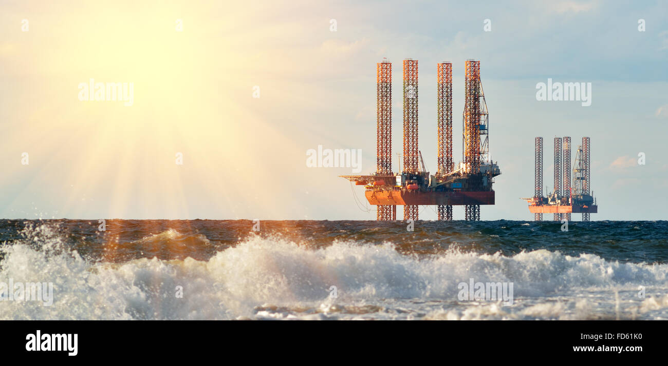 Sea station of gas production. Drilling platforms in the sea at sunrise against a blue sky - Stock Image