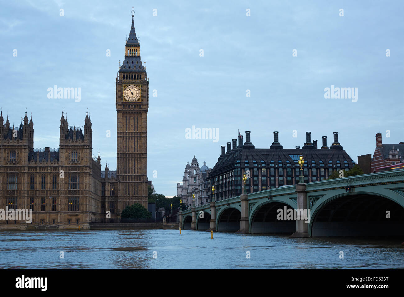 Big Ben and bridge, traffic on bridge at dusk in London, natural light and colors in the early cloudy morning in - Stock Image