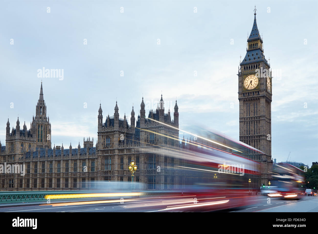 Big Ben and Palace of Westminster in the early morning, red buses passing in London, natural colors and lights - Stock Image