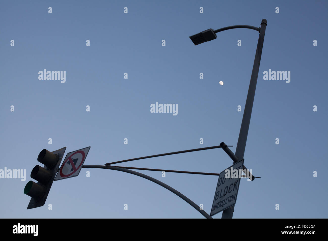 Low Angle View Of Road Sign With Street Light Against Clear Sky At Dusk Stock Photo