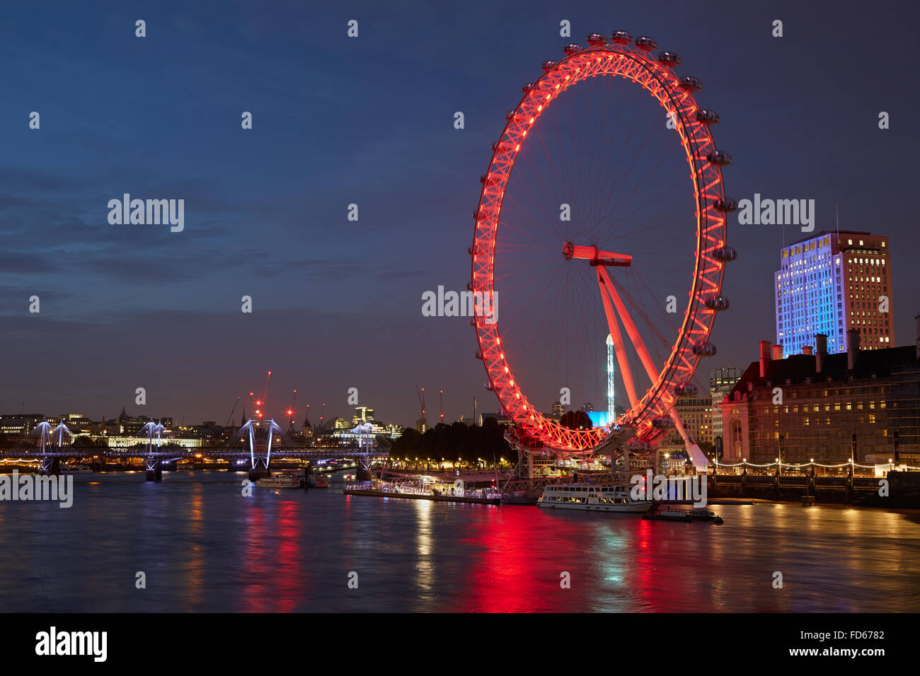 London eye, ferris wheel, illuminated in red and Thames river view in the night - Stock Image