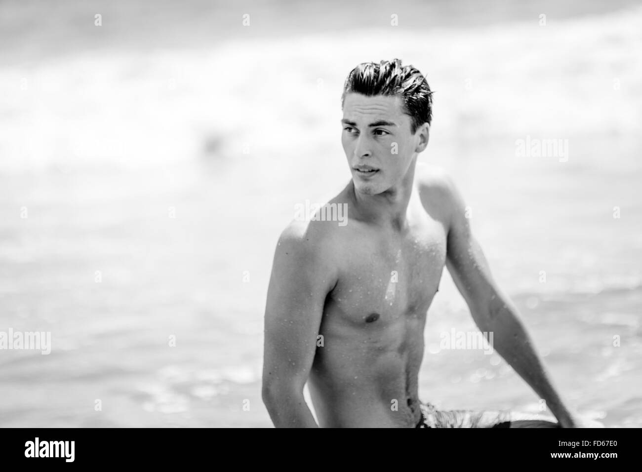 Young Man Sitting At Beach While Looking Away - Stock Image