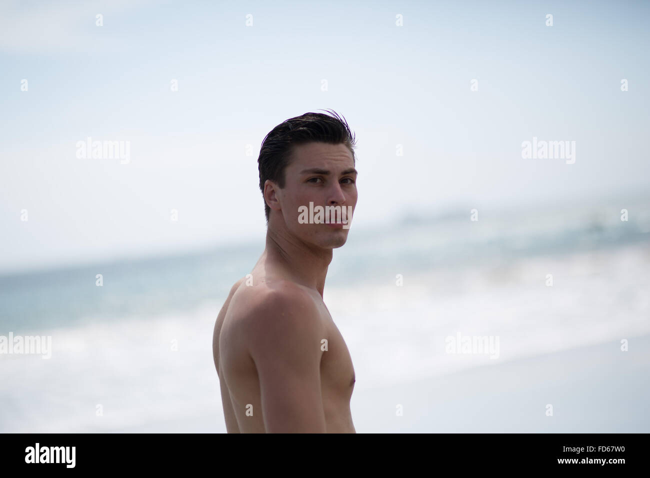 Portrait Of Handsome Young Man Standing At Beach - Stock Image