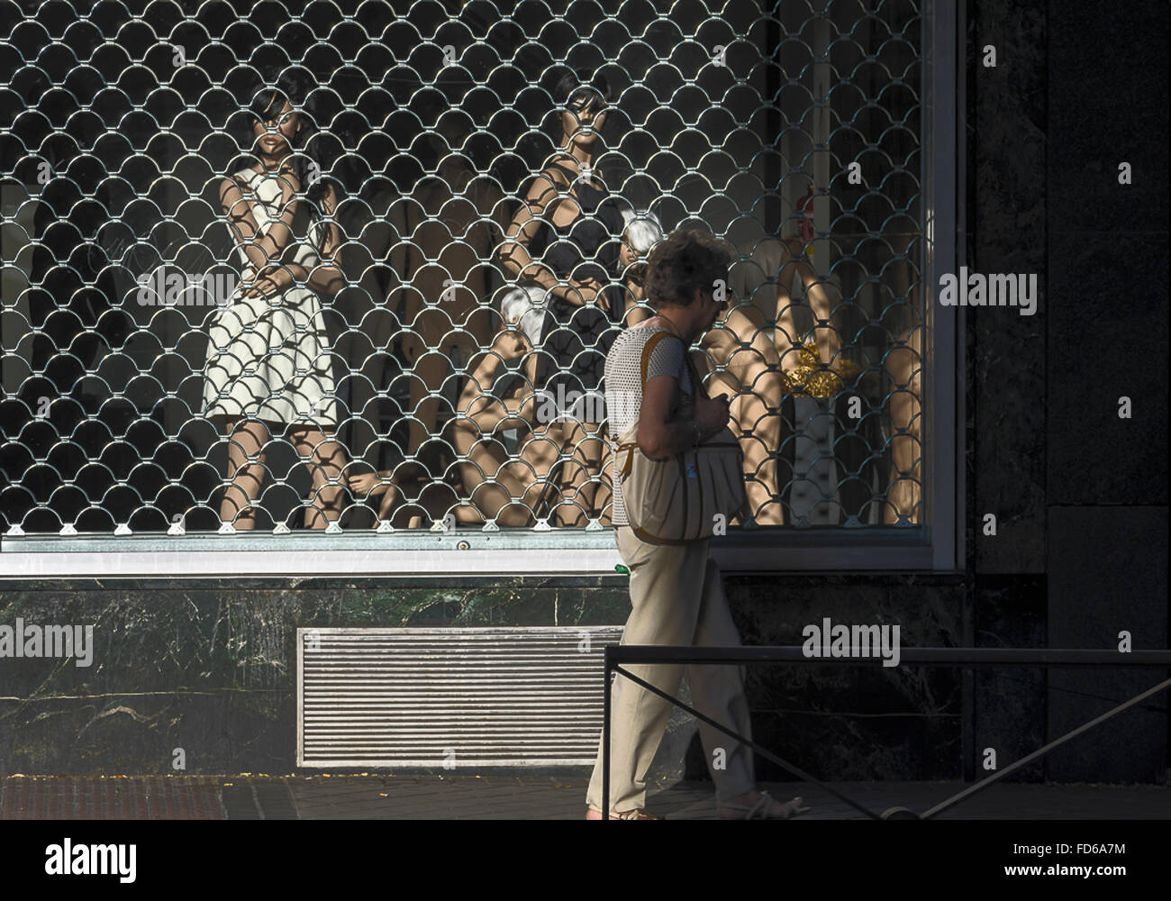A old woman crossing a shop window with models in shadows in a street of Madrid, Spain - Stock Image
