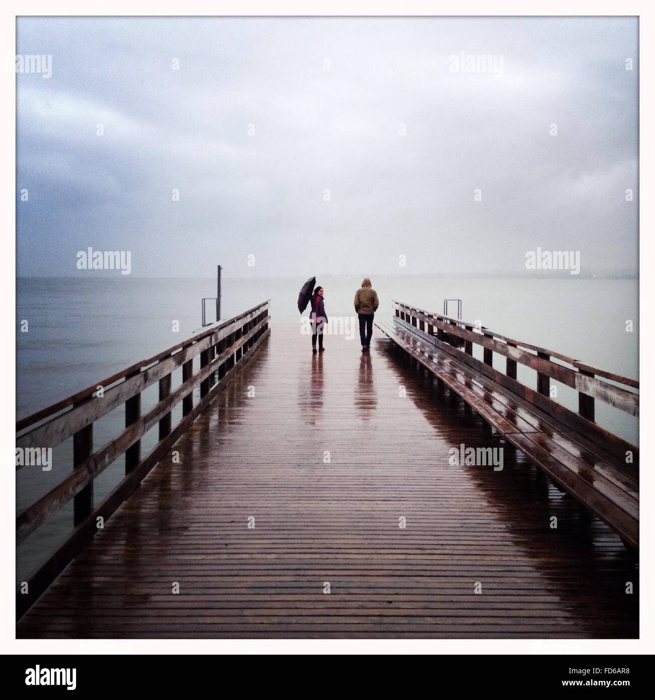Couple Walking At A Pier - Stock Image