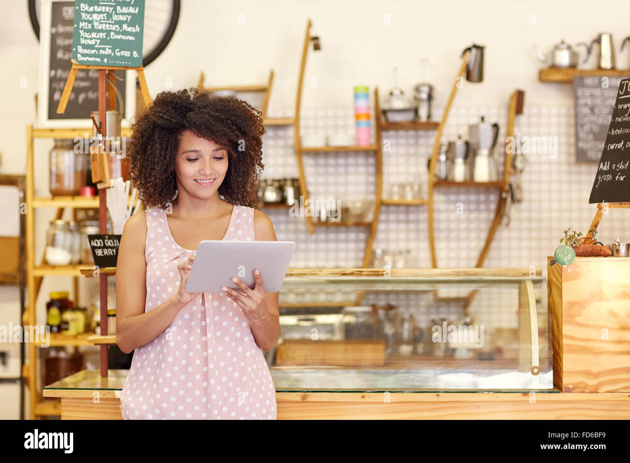 Small business owner using a tablet in her coffee shop - Stock Image