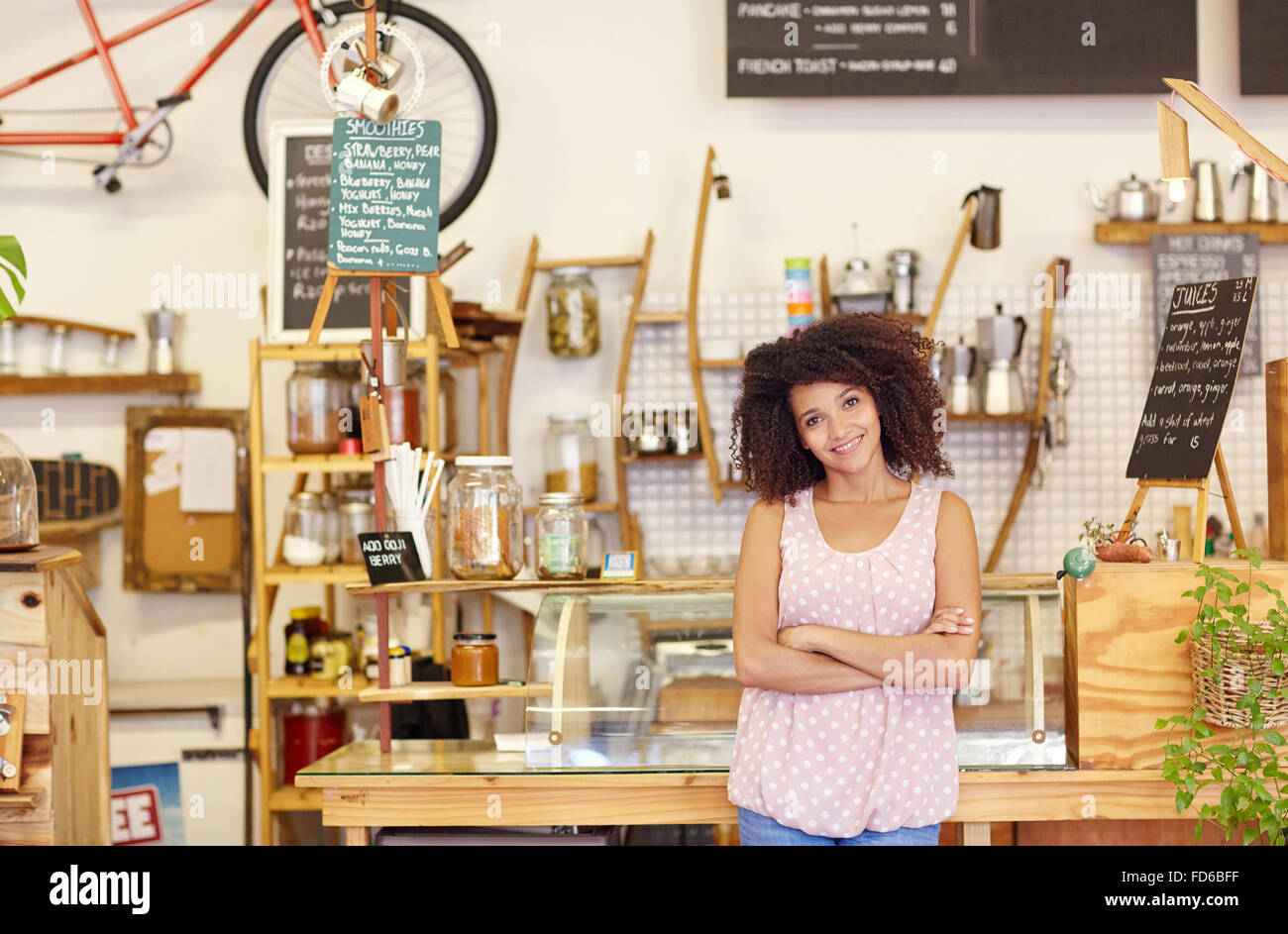 Small business owner standing proudly in her coffee shop - Stock Image