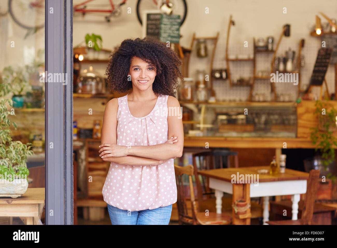 Small business owner standing in the door of her coffee - Stock Image