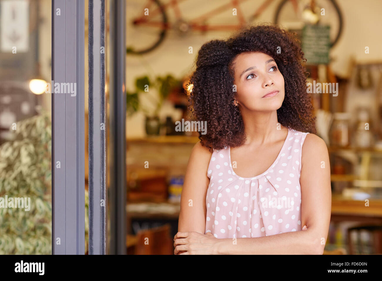Small business owner standing and thinking - Stock Image