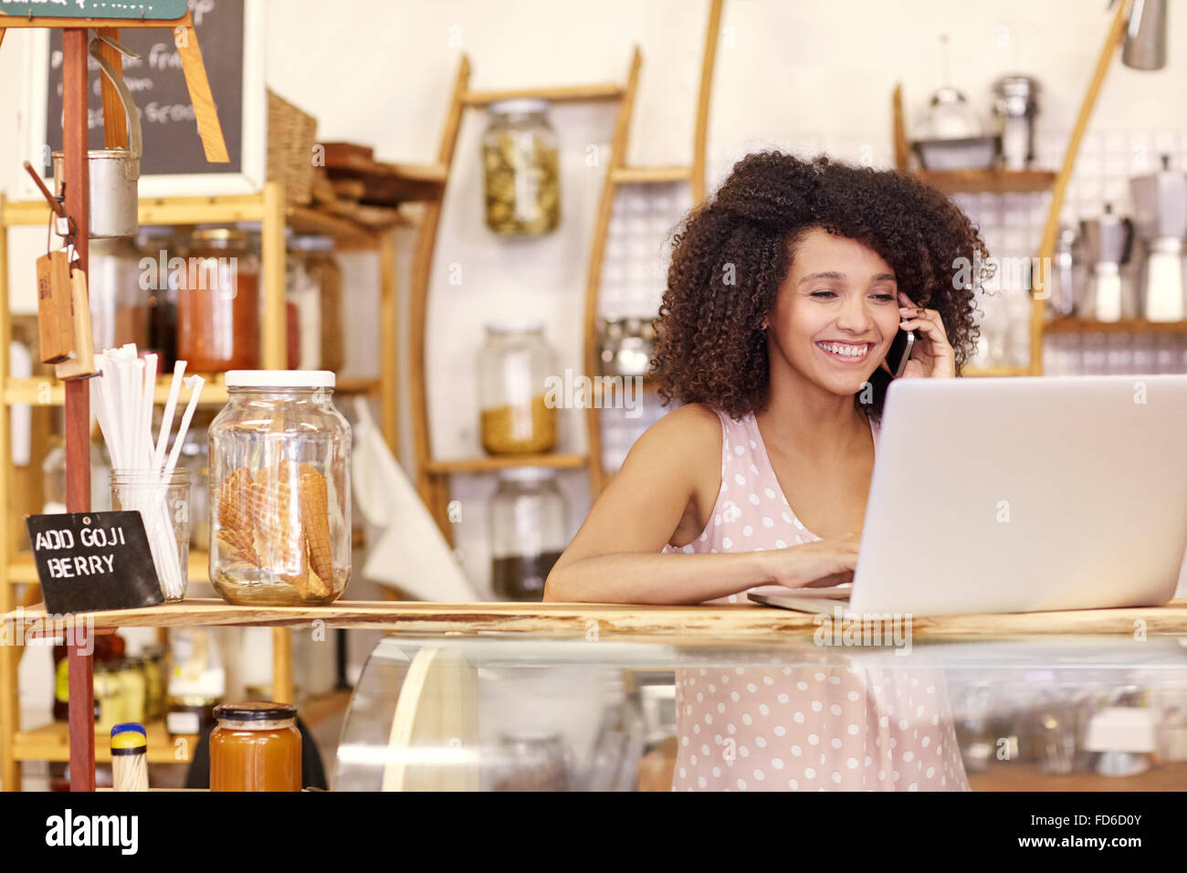 Smiling coffee shop owner typing on a laptop while talking - Stock Image