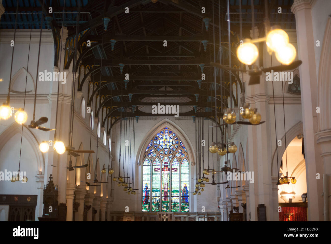 Hanging Lights Against Strained Glass Window At Church - Stock Image