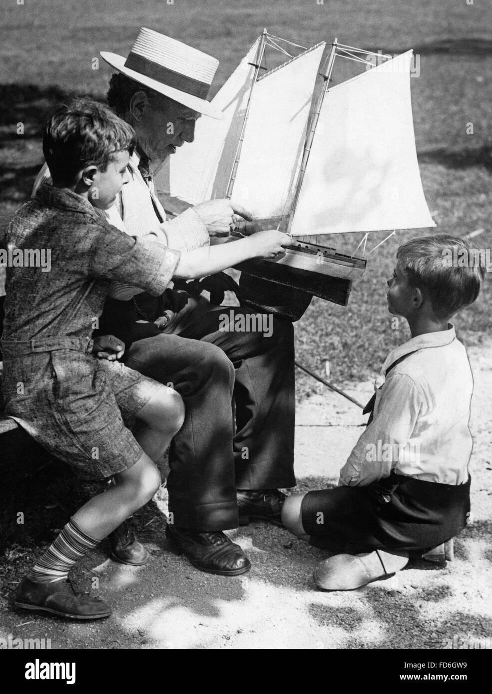 Man and boys with a model of a ship, 1930s - Stock Image