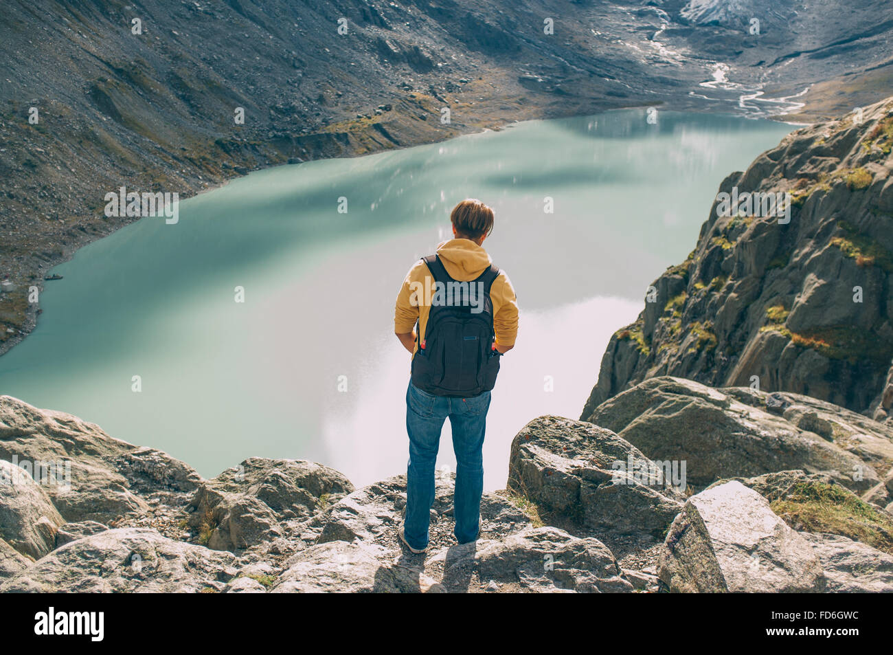Young Man Looking At Mountain Lake From Elevated Spot - Stock Image