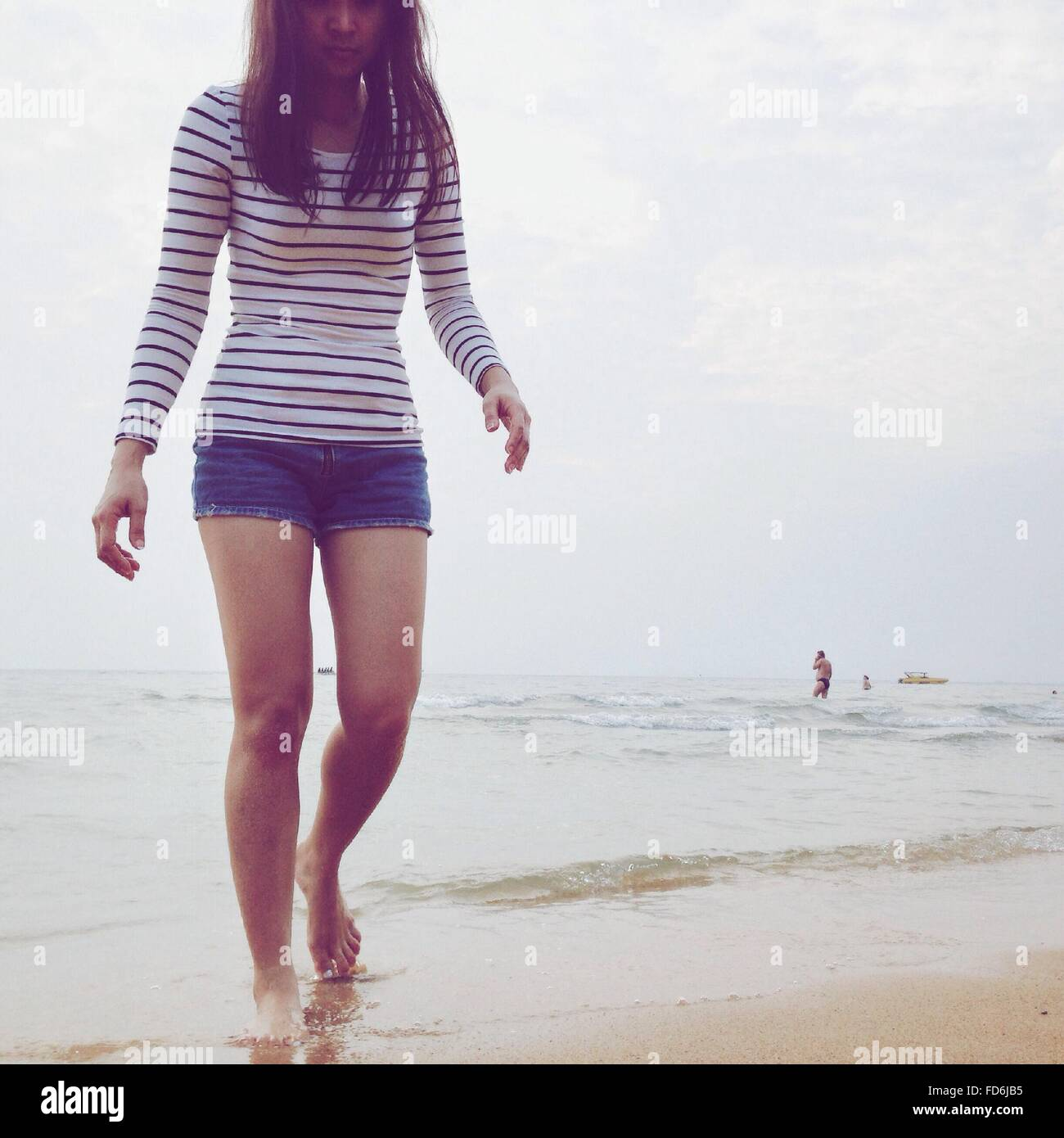 Young Woman Walking On Beach - Stock Image