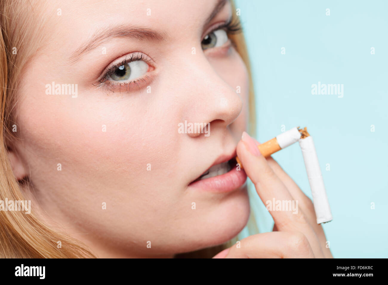Smilling pretty girl smoking breaked down cigarette. Winning with addicted nicotine problems in young age. - Stock Image