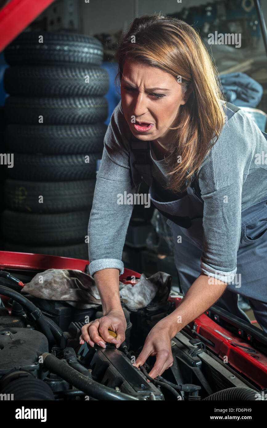Young stressful female car mechanic in auto repair service, red automobile with tire in background - Stock Image