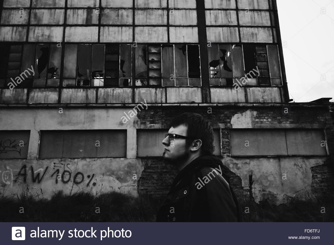 Man Walking Against Abandoned Building Stock Photo Alamy