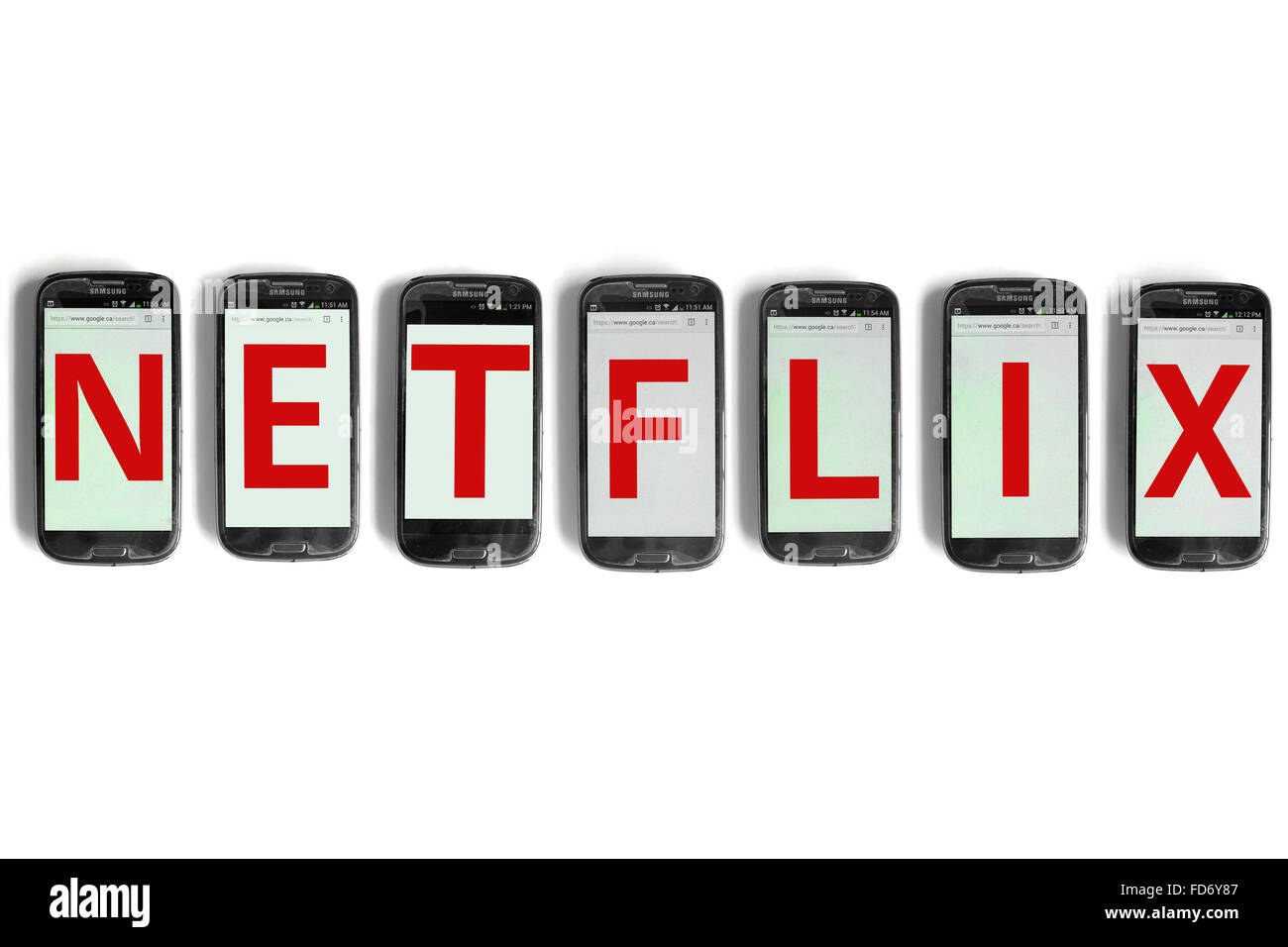 Netflix spelled on the screens of smartphones photographed against a white background. - Stock Image