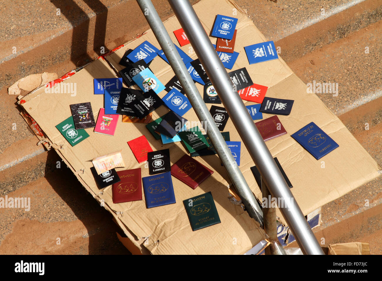 Identity cards in booklets for sale on the steps in Kampala, Uganda. - Stock Image