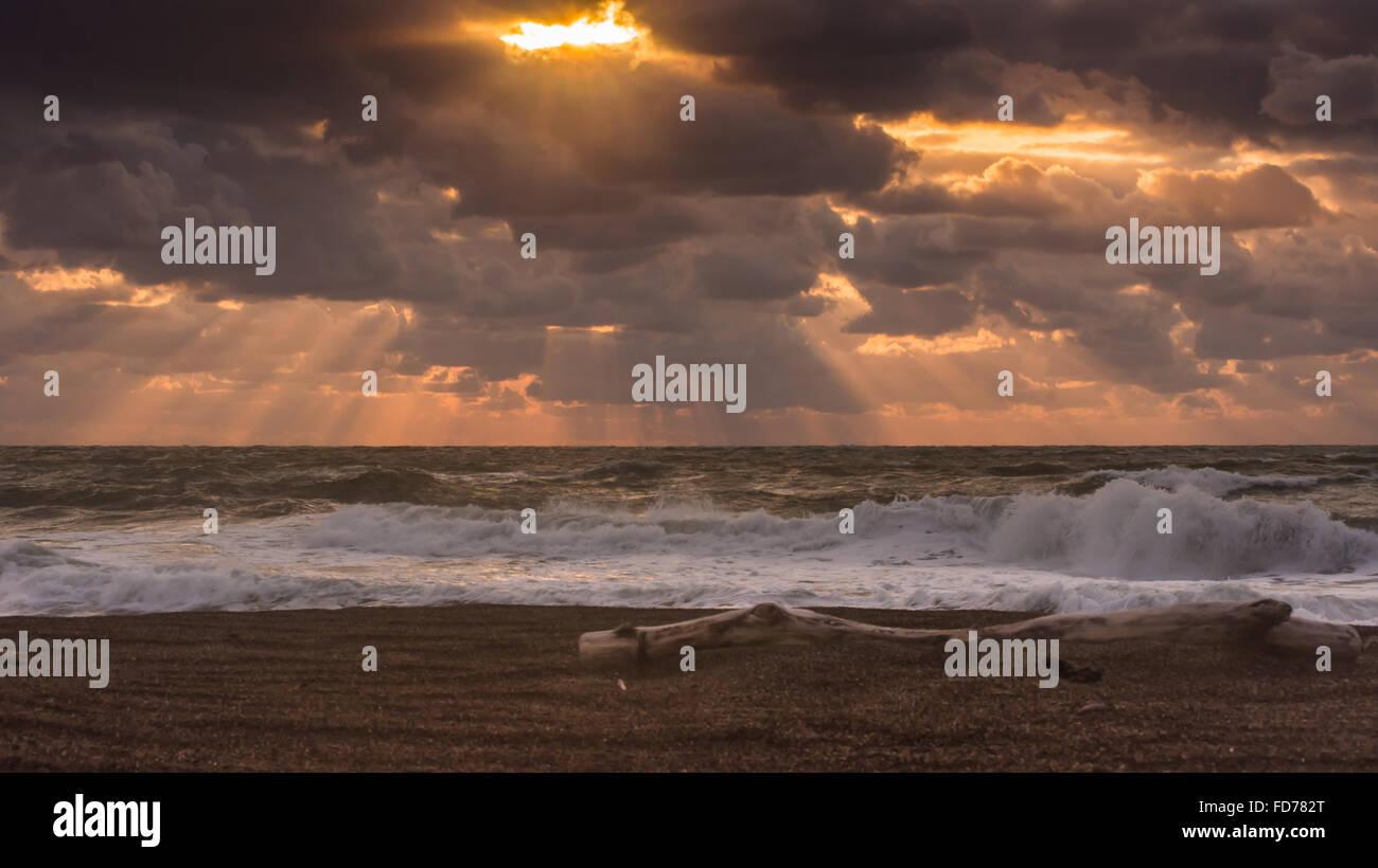 Sunlight Piercing Through Clouds Onto Sand Beach - Stock Image