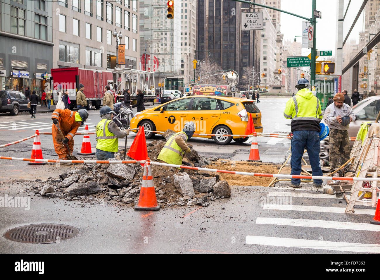 Public workers digging a hole on the street of New York City to perform repair - roped off to secure the area Stock Photo