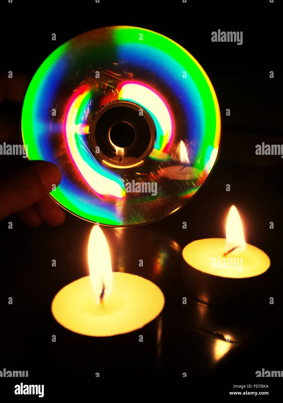 Candlelight Reflecting In Compact Disc - Stock Image